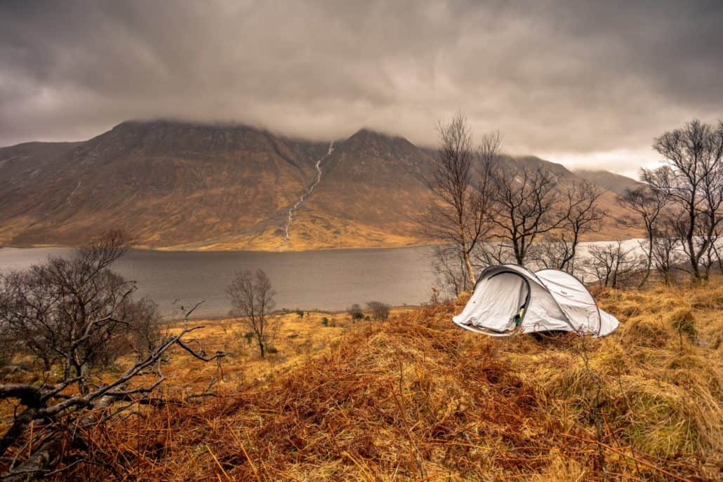 A tent cot set up in a dry field with a lake and mountain in the background