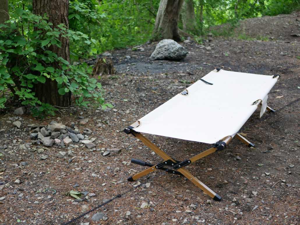 A white cot set up in the wilderness