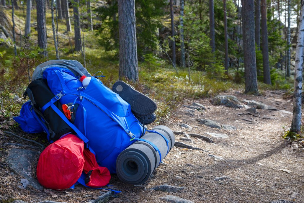 A blue backpack with sleeping pad and shoes leaning against the side of a trail in a forest