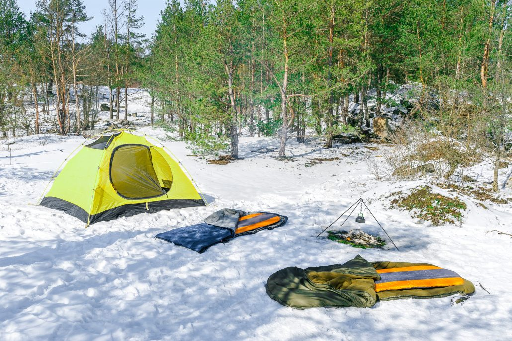 A tent set up on the snow with two sleeping bags outside by a camp fire