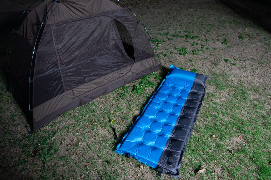 Small Camping Tent and a blue air bed on a Grass field at Night Hours Campsite