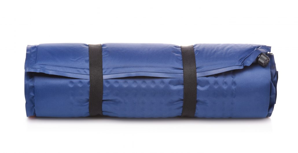 Front view of rolled blue self-inflating foam camping mattress isolated on white