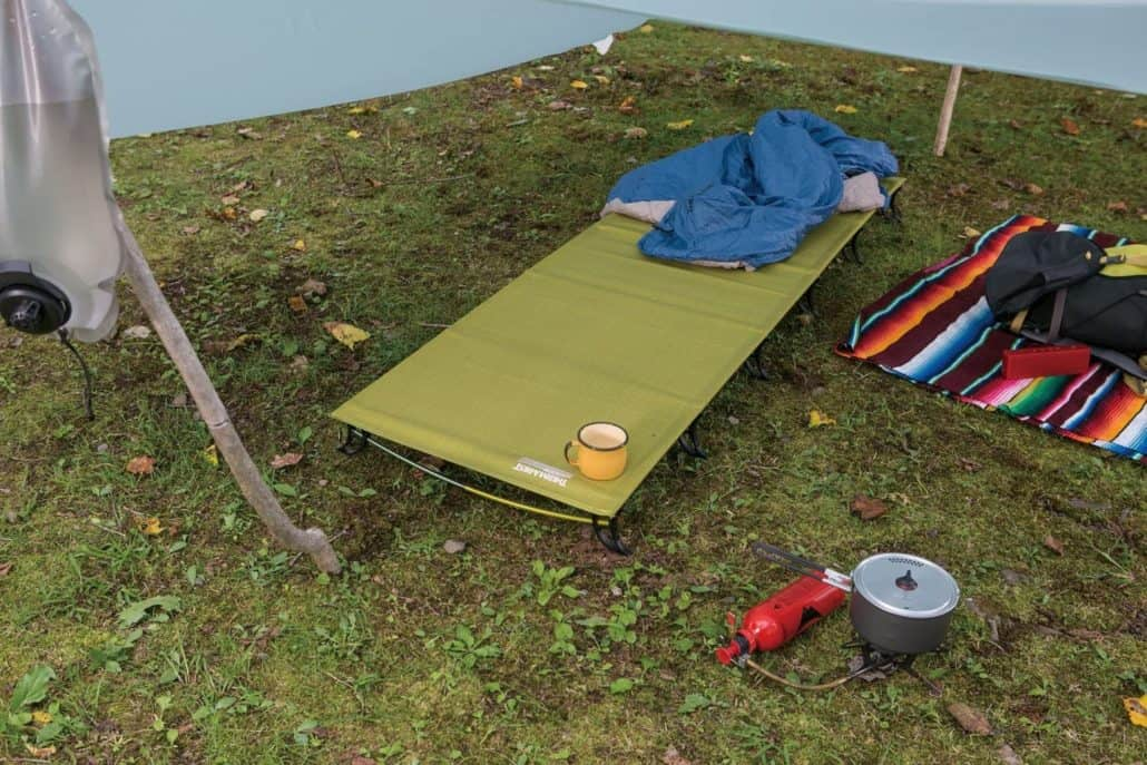 Backpacking cot inside a tarp with other camping gear